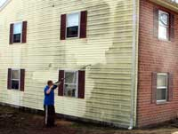 Before and after picture of siding being power washed.